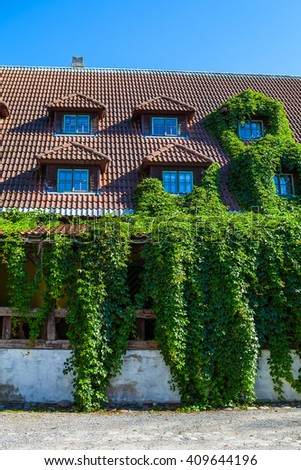 Ivy covered beautiful old stone house with tiled roof and small windows. Parnu, Estonia - stock photo