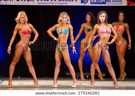 Izhevsk, Russia - April 18, 2015. Open championship of the Volga Federal District of bodybuilding and fitness bikini. Girls in bright bikini on body fitness competitions - stock photo