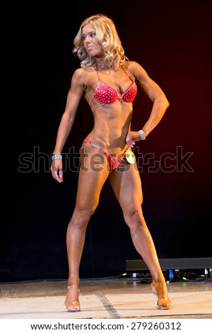 Izhevsk, Russia - April 18, 2015. Open championship of the Volga Federal District of bodybuilding and fitness bikini. Blonde in a red bikini on competition bodifitness - stock photo