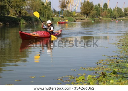 IZMAIL, UKRAINE - SEPTEMBER 13, 2015: Kayaking competition Boy in red kayak with yellow paddle