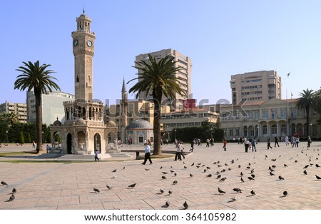 IZMIR, TURKEY - OCTOBER 1, 2009: Historical clock tower, mosque and palm trees on Konak Square  - stock photo