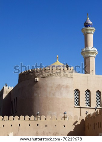 Jabreen castle and a minaret mosque near Nizwa in the Sultanate of Oman in the Middle East - stock photo