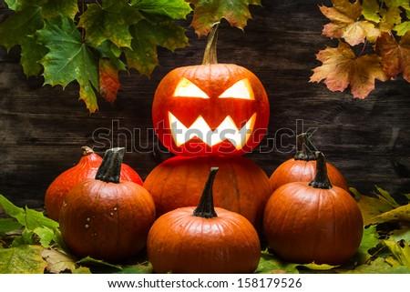 Jack o lantern on pumpkins pile - stock photo