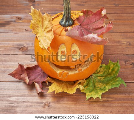 Jack o lantern smiling happy pumpkin composition over the maple leaves and wooden surface - stock photo