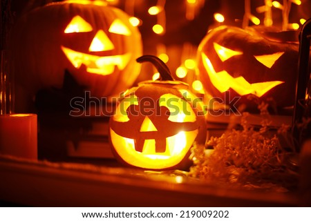Jack-o-lanterns and other Halloween objects in a window - stock photo