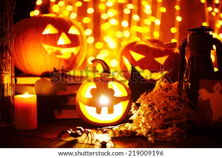 Jack-o-lanterns and other Halloween objects on sparkling background - stock photo