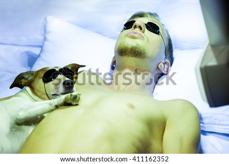jack russell dog  and owner tanning under the home solarium on bed, or sun tanning studio, eyes closed sleeping or resting - stock photo