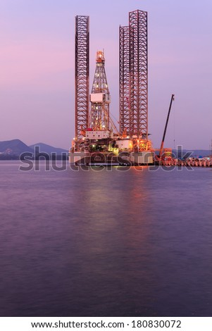 Jack up oil drilling rig in the shipyard for maintenance at sunset time