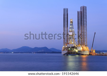 Jack up oil drilling rig in the shipyard for maintenance at sunset time - stock photo