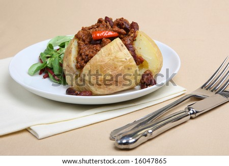 Jacket potato stuffed with Chilli con Carne - stock photo