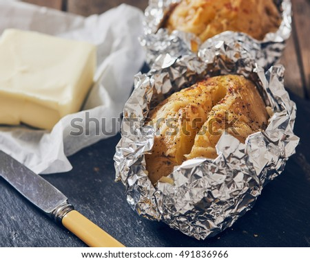 jacket potatoes with provola cheese wrapped in an aluminium foil on a slate plate