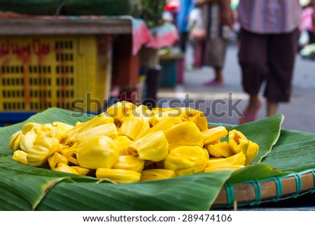 Jackfruit yellow seedless pile on green banana leaf tray for sale in the market place.