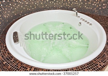 Jacuzzi with Swirling water and mosaic in Bathroom - stock photo