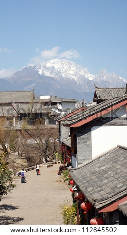 jade dangon snow mountain behind the street of  lijiang old town, the world heritage site of UNESCO  - stock photo
