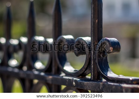 Jagged iron fence with blurry background