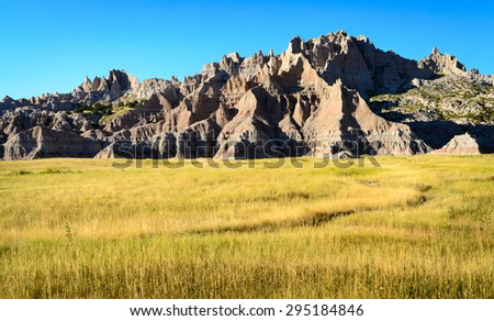 Jagged Rock Formations in Field at Badlands National Park - stock photo