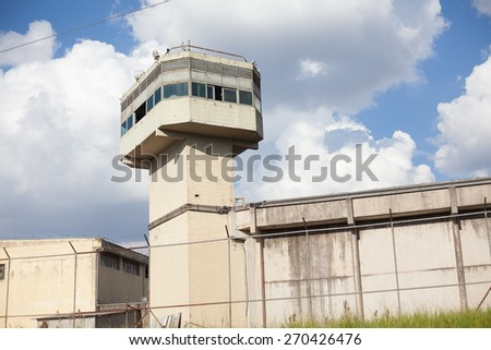 Jail tower and walls surrounded by gate - stock photo