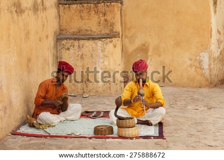 JAIPUR, INDIA - APRIL  22, 2015: A snake charmer is playing the flute for the cobra sitting by the wall in the Fort Amber on April 22, 2015 in Jaipur, India. - stock photo