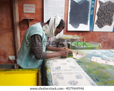 Jaipur, INDIA â?? December 27, 2014: Unidentified craftsman printing a wooden printing block for textile.