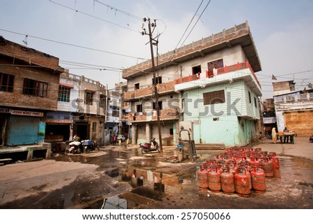 JAIPUR, INDIA - JAN 25: Gas cylinders put on a dirty street with old houses of poor families on January 25, 2015. Jaipur, with population 6,664000 people, is a capital of Rajasthan - stock photo