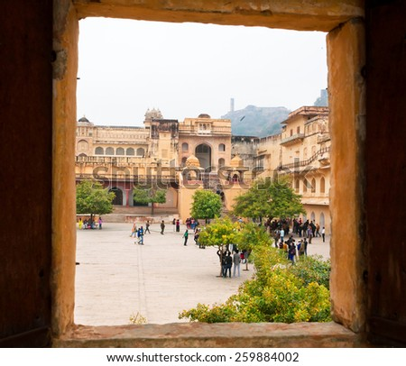 JAIPUR, INDIA - JAN 23: Open window of the Amber Fort and people walking around the historical stone palaces on January 23, 2015 in Rajasthan. Amber Fort was built in 1592 by rajput Raja Man Singh.