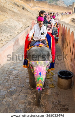 JAIPUR, INDIA - JAN 19, 2016: Unidentified tourists ride an elephant. Indian elephants used to be one of the main way of transportation in the past
