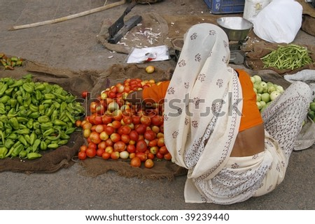 JAIPUR, INDIA - JUNE 20: An unidentified woman sells local produce June 20, 2007 in Jaipur, India. Biggest health risks in India are hep B and typhoid, the main source being contaminated unclean food. - stock photo