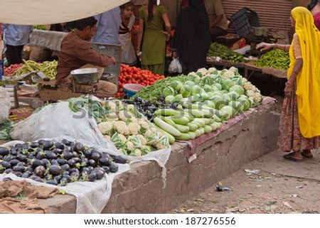 JAIPUR, INDIA - MARCH 26, 2014: Trader and customer at a stall in the fruit and vegetable market in the old Johari Bazaar district of the city - stock photo