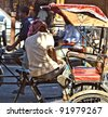 JAIPUR, INDIA - NOVEMBER 12: man rests in his Cycle rickshaw on November 12, 2011 in Jaipur, India. Cycle rickshaws were introduced in the 1940's and have a fixed quota of licenses. - stock photo