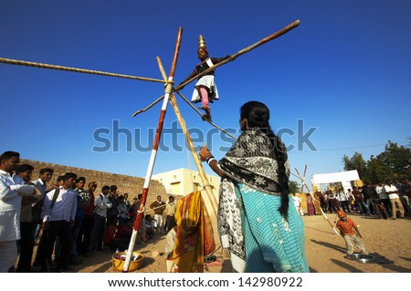 JAISALMER, INDIA-FEB 24: an unidentified girl performs an acrobat on Feb 24, 2013 in Jaisalmer, India.The event is part of the Desert Festival held to attract both domestic and international tourists. - stock photo