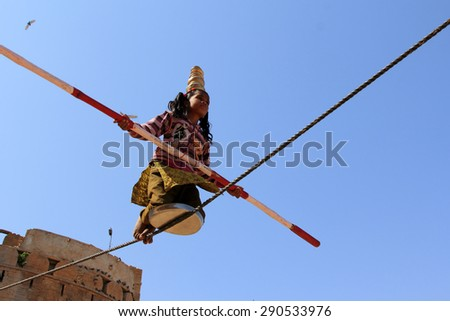 JAISALMER, INDIA - FEB 03, 2015: An unidentified Indian girl performs street acrobatics by walking the rope during the Desert Festival on February 03,2015 in Jaisalmer, Rajasthan, India.
