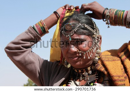 JAISALMER, INDIA - FEB 03: Unidentified tribal woman dressed up in traditional Rajasthani costume and ornaments poses during Desert Festival on February 03, 2015 in Jaisalmer, Rajasthan, India. - stock photo