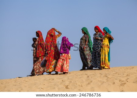 Jaisalmer, India - February 25, 2013: Camel riding at the Sam Sand Dune. The activity is part of the Desert Festival held in winter to attract both domestic and international tourists. - stock photo
