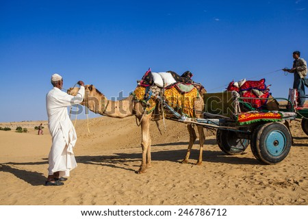 Jaisalmer, India - February 25, 2013: Cameleer at the Sam Sand Dune. Camel riding activity for tourists is another income source for desert villagers apart from farming and animal raising - stock photo