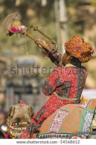 JAISALMER, INDIA - FEBRUARY 19: Man in colorful tunic blowing a trumpet whilst riding a camel in the parade at the start of the Desert Festival on February 19, 2008 in Jaisalmer, Rajasthan, India - stock photo