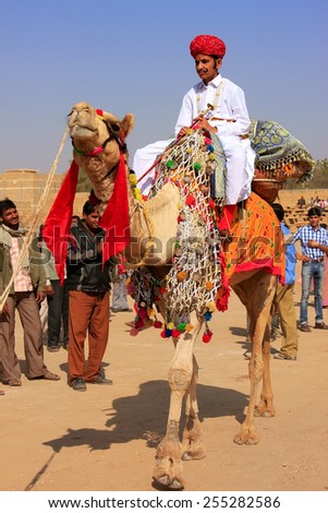 JAISALMER, INDIA - FEBRUARY 17: Unidentified boy rides camel during Desert Festival on February 17, 2011 in Jaisalmer, India. Main purpose of Festival is to display colorful culture of Rajasthan - stock photo