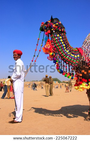 JAISALMER, INDIA - FEBRUARY 16: Unidentified man stands with camel during Desert Festival on February 16, 2011 in Jaisalmer, India. Main purpose of Festival is to display colorful culture of Rajasthan - stock photo