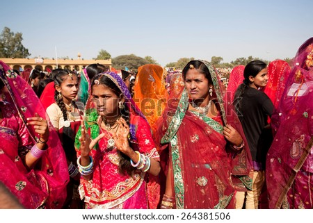 JAISALMER, INDIA - MAR 1: Adorable girls in colors sari dresses come with emotions through the crowd of Desert Festival on March 1, 2015 in Rajasthan. Every winter Jaisalmer takes the Desert Festival - stock photo