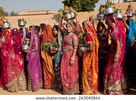 JAISALMER, INDIA - MAR 1: Beautiful dressed women in carry water in jugs and fruits on the famous Desert Festival on March 1, 2015. Every winter Jaisalmer takes the Desert Festival of Rajasthan - stock photo