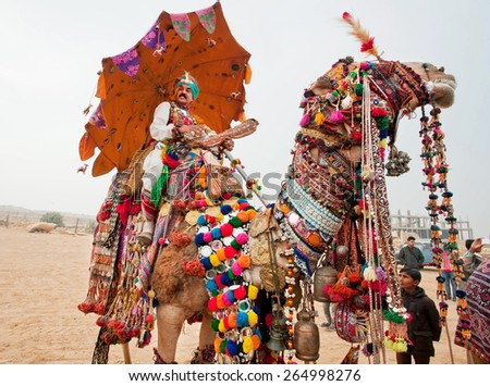 JAISALMER, INDIA - MAR 2: Camel driver riding on the rural show during the famous Desert Festival on March 2, 2015. Every year in the february Jaisalmer takes the village Desert Festival