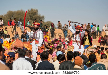 JAISALMER, INDIA - MAR 1: Camel riders with swords happy to see many people in the crowd of the popular Desert Festival on March 1, 2015 in Rajasthan. Every winter Jaisalmer takes the Desert Festival - stock photo