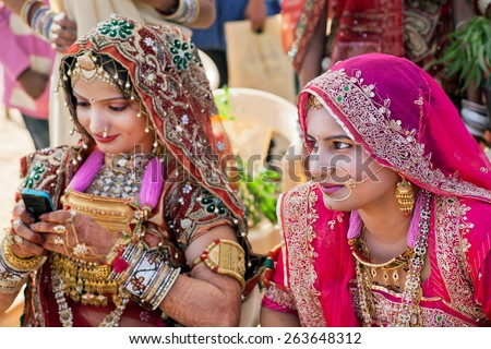 JAISALMER, INDIA - MAR 1: Women in beautiful indian dresses and gold jewelry sitting in shadow on the Desert Festival on March 1, 2015 in Rajasthan. Every winter Jaisalmer takes the Desert Festival - stock photo