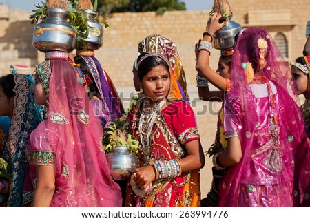JAISALMER, INDIA - MAR 1: Young woman thinking about something in a crowd of girls dressed in sari on the Desert Festival on March 1, 2015. Every winter Jaisalmer takes Desert Festival of Rajasthan - stock photo