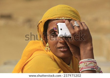 JAISALMER,INDIA - November 9,2014 : Unidentified indian woman sits and keeps a cell phone in hand. - stock photo