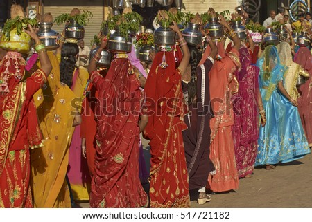 JAISALMER, RAJASTHAN, INDIA - FEBRUARY 19, 2008: Group of young Indian woman in brightly colored clothing carrying pots  and plants on their heads as part of the annual Desert Festival.