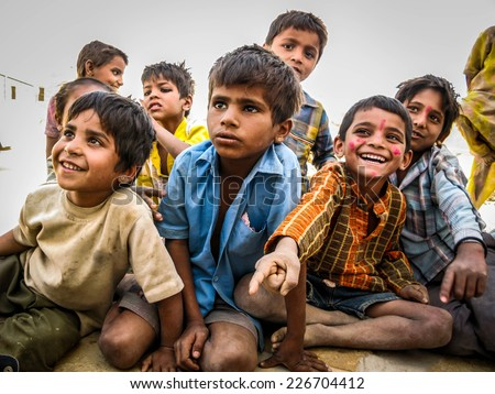 Jaisalmer, Rajasthan, India - March 27: Happy Indian children sitting out, smiling, at desert village in Jaisalmer, Rajasthan, India.  - stock photo