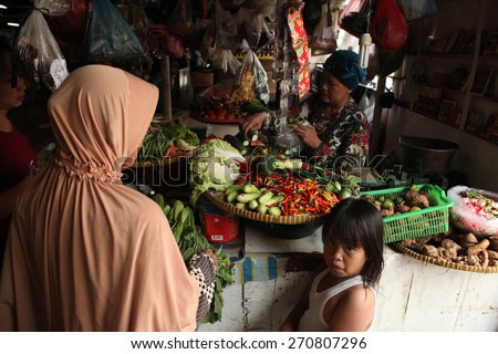 JAKARTA, INDONESIA - AUGUST 17, 2011: Vendor sells vegetables at the Pasar Pramuka Market in Jakarta, Central Java, Indonesia. - stock photo