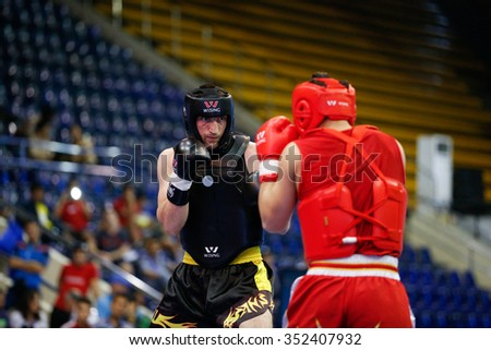 JAKARTA, INDONESIA - NOVEMBER 18, 2015: Bagdat Kenzhetayev of Kazakhstan (red) fights Muslim Salikhov of Russia (black) in the men's 80kg Sanda event at the 13th World Wushu Championship 2015. - stock photo