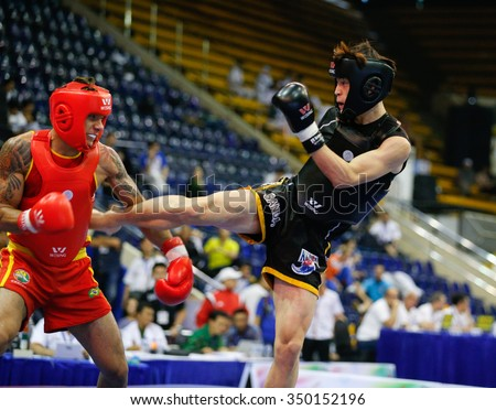 JAKARTA, INDONESIA - NOVEMBER 16, 2015: Caio Pitoli of Brazil (red) fights Youngkyu Ko of South Korea (black) in the men's 70kg Sanda event at the 13th World Wushu Championship 2015. - stock photo