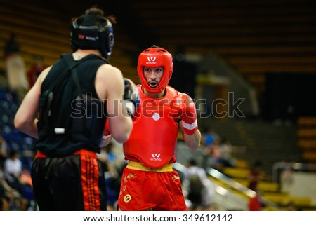 JAKARTA, INDONESIA - NOVEMBER 15, 2015: Esteban Bovea of Spain (red) fights Michael Lee of USA (black) in the men's 70kg Sanda event at the 13th World Wushu Championship 2015 in Istora Senayan. - stock photo